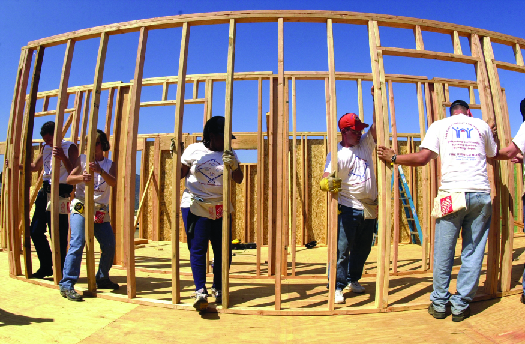 An image of several people working together to build the wooden framework of a building.
