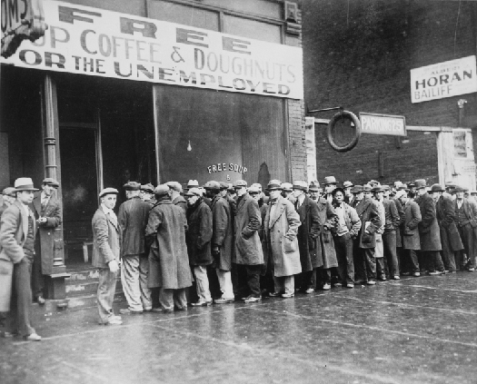 """Photo shows a line of people in long coats and hats standing in line outside a building with a sign that states """"Free Cup Coffee & Doughnuts for the Unemployed""""."""
