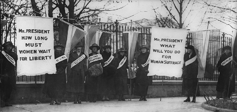"An image of several people standing in front of a fence. Some people are holding banners. The banners read ""Mr. President how long must women wait for liberty"" and ""Mr. President what will you do for woman sufferage""."