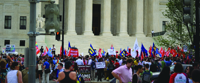 An image of a group of people standing in front of a building. Some people are holding signs.