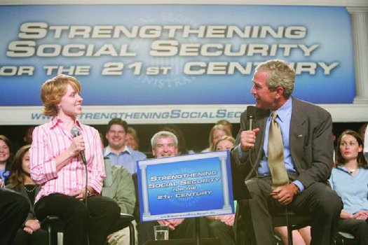 "A photo of George W. Bush speaking at an event. The banner behind him says ""Strengthening Social Security for the 21st Century."""