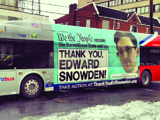 "An ad on the side of a bus featuring a photo of Edward Snowden. The text says ""We the people oppose the Surveillance State and say 'Thank you, Edward Snowden!'"""
