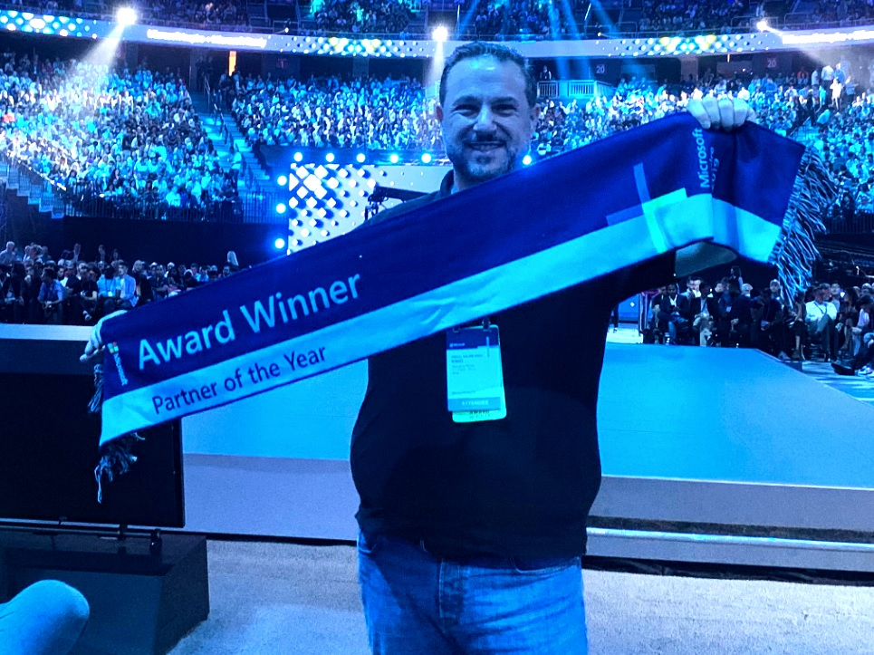 a man holds an award sash across his chest in front of a blue-lit arena full of people