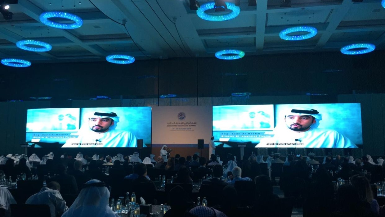 shows a large room filled with delegates watching two presentation screens