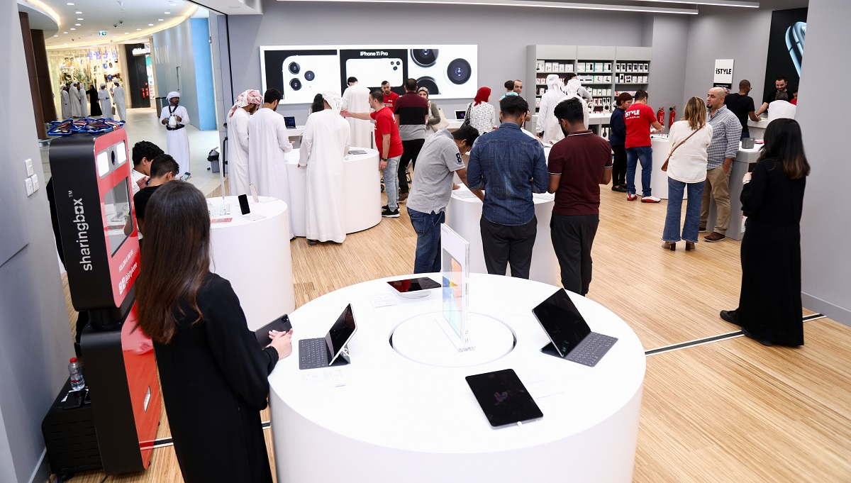 shows a round white display stand with phones and tablets, with guests at the launch in the background