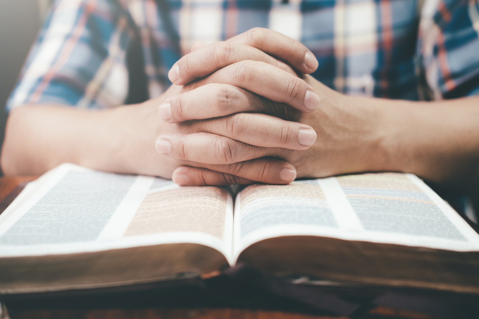 Man praying, hands clasped together on his Bible.