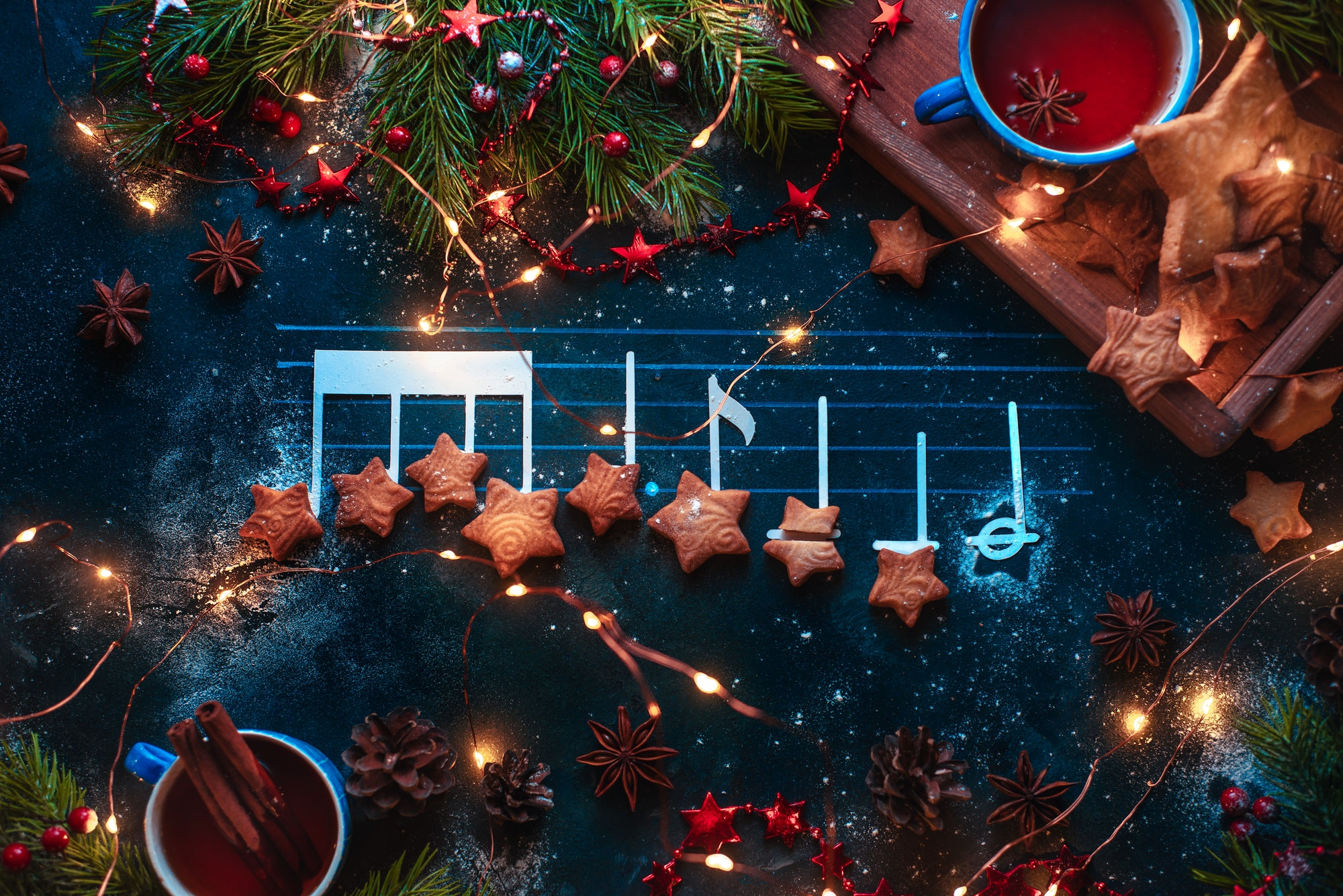 Christmas melody notes flat lay with star-shaped cookies, fir tree branches, wooden tray, anise