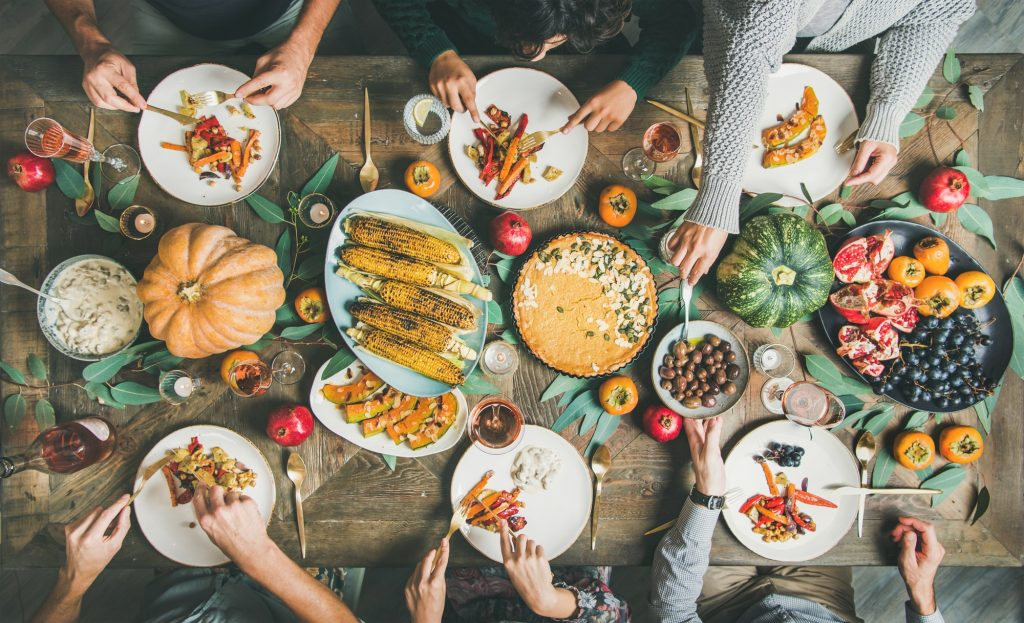Friends eating at Thanksgiving Day table with vegetarian meals