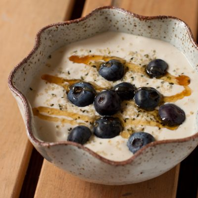 Cashew yogurt topped with honey, blueberries, and hemp seeds