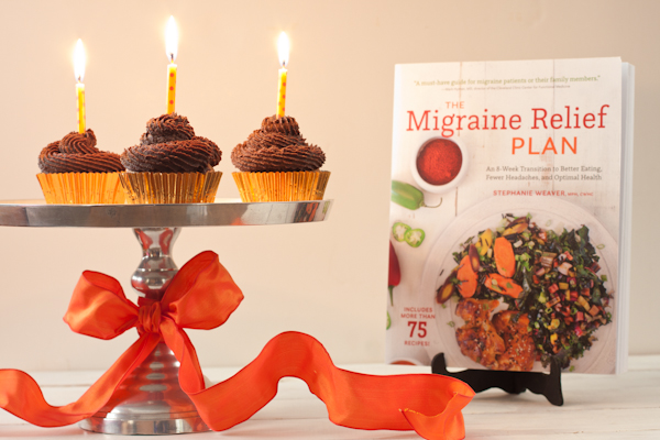 Cupcakes on a cake stand with lit candles and The Migraine Relief Plan book