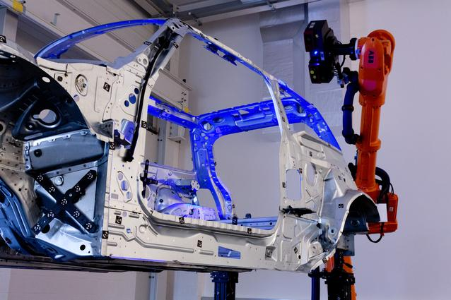 Camera measurement system checking dimensional accuracy of a mid-build car body shell.