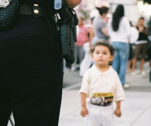 Yananthe, daugther of Norma Marquez, looks on as police officers attend the vigil.