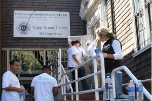 Volunteers paint the banister at the Capp Street Center entrance.