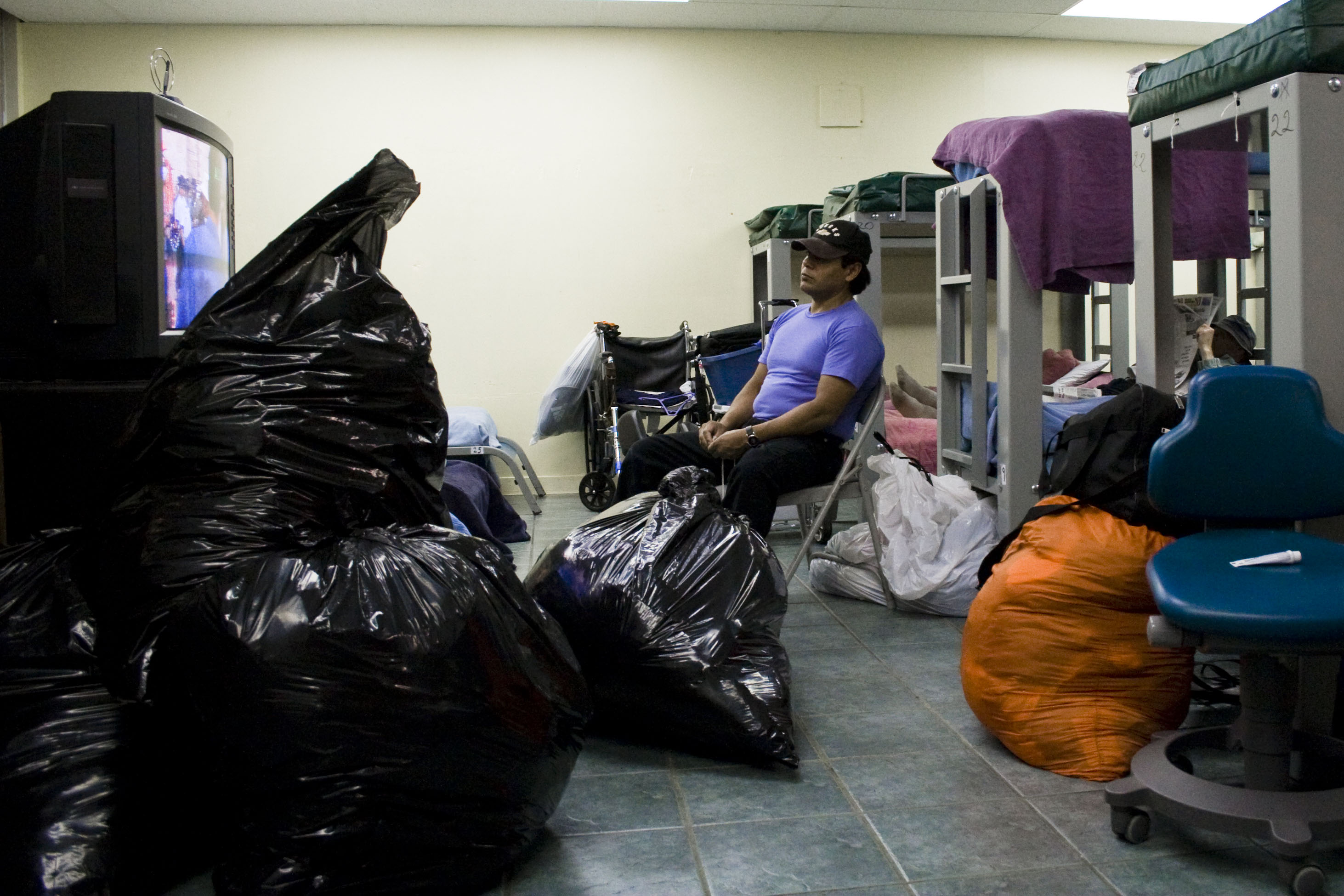 A man watches television amid trash bags of belongings in the shelter on 21st and Capp streets.