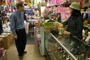 FEW CUSTOMERS: Maisie Wong (right) talk to his husband, Check Chew Ng as two customers take a look at goods in their store. Wong said her store sales continued to plunge, so she had no choices but to fire all her two employees. (Moch. N. Kurniawan)