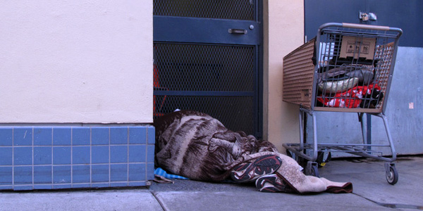 A man sleeps in a doorway on Caledonia Street, just around the corner from businesses on 16th Street.