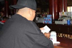 patron at Carlos Bar on 24th Street and Mission reads a pamphlet