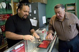 Jorge Garcia, left speaks with a Damaso Ramirez, a customer at the La Guadelupana jewelry store on Mission Street.