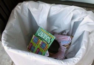 A garbage full of losing lottery tickets and scratchers.