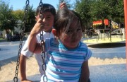Emily Vasquez, 4, and Brandon Aguilar, 10, take a ride on the tire swing at Parque Niños Unidos last weekend. The park is one of many in the Mission where programs and hours have been cut.