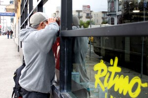 A passerby stops by the former Ritmo Latino location to peer into the abandoned store.