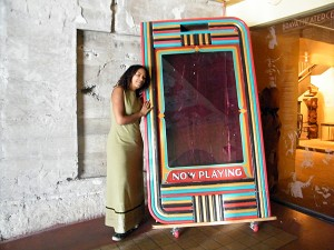 "Artistic director Raelle Myrick-Hodges leans against a vintage ""Now Playing"" sign at the Brava Theater on 24th Street."