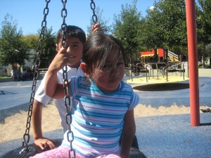 Emily Vasquez, 4, and Brandon Aguilar, 8, take a ride on the tire swing at Parque Niños Unidos last weekend.