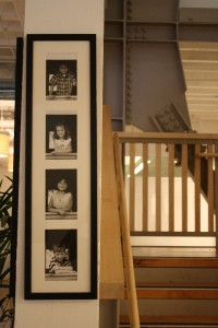 Photos of the founding kindergarten class line a post by the main stairwell, which is made from repurposed beams.