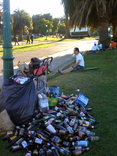 Dolores Park bottle collection with police in the distance (Photo by: Heather Duthie)