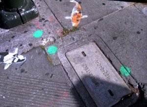 Sidewalk art fish intermingle with dots left behind by the Department of Public Works, signaling where repairs are needed.