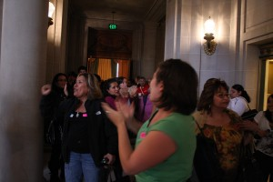 "Audience members chant ""si se puede(yes we can)"" outside the chamber."