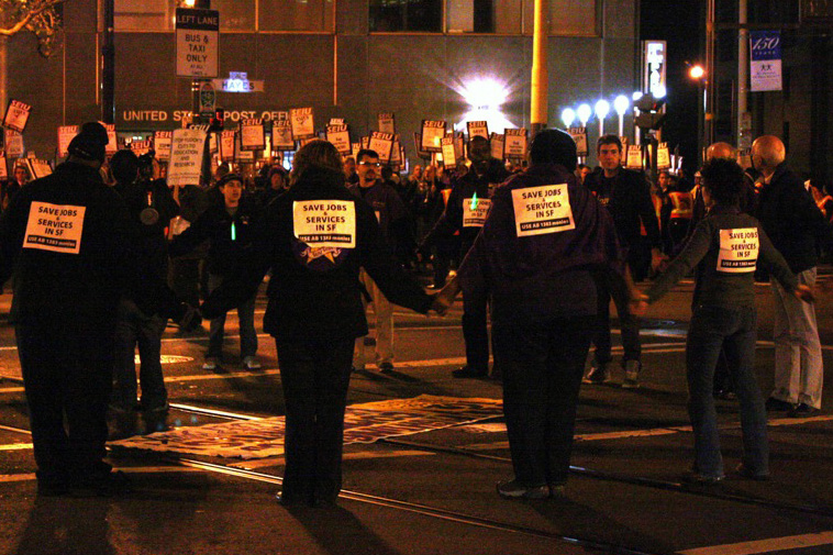 SEIU protestors outside City Hall on Monday night demand cuts public health workers be restored.