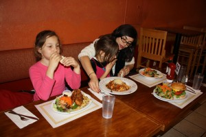 Nikki Kourmouzis, 36 sits next to her daughter Zoe, 6, while daughter Eva starts eating dinner.