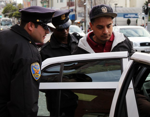 Officers Luis Prieto (L) and Joseph Obidi arrest a man for public urination near Mission and 24th Streets.