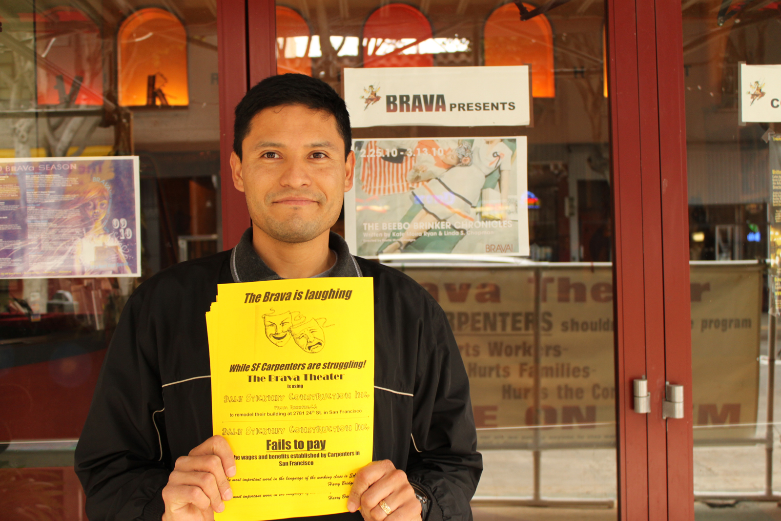 An unemployed carpenter hands out flyers in front of Brava.