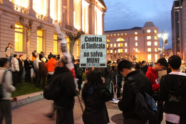 Marchers merged on city hall Monday night to protest the Muni service reductions made last Friday.