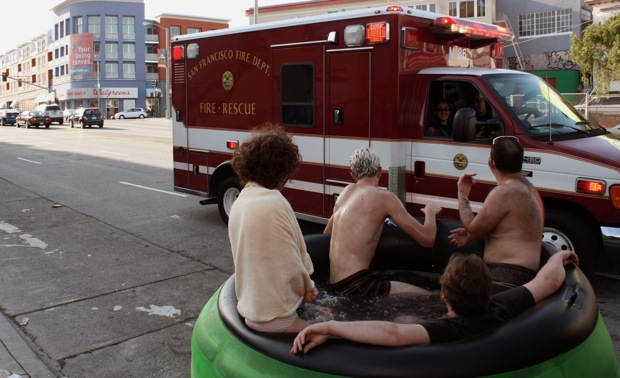 An improvised hot tub on Caesar Chavez attracts the attention of some paramedics.
