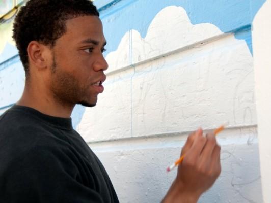 "Artist Uzomah ""Uzz"" Chiagoroh worked on the community mural on Bartlett."