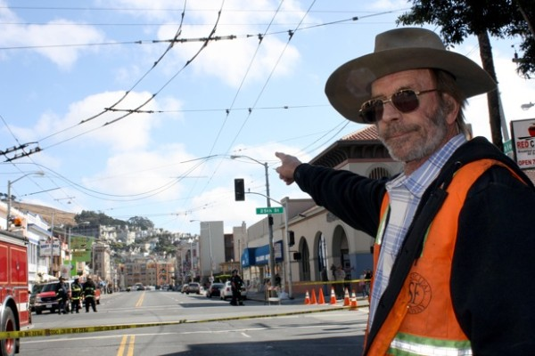 Muni journeyman John Scott points towards the electrical lines draped across Muni cables at Mission and 25th. Photo by Caroline Bins.
