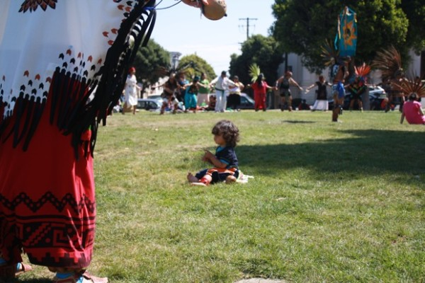 Quetzalcoatl Sandoval sits patiently as his mother Sandra Sandoval takes part in the Aztec dancing.