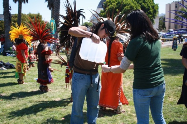 Genaro Rios helps pass out water to the dancers.