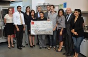 """Philip Clark, wearing sandals, receives a check from Wells Fargo for winning La Cocina's website design contest. Nearly 300 people """"liked"""" the site he built for El Huarache Loco on Facebook."""