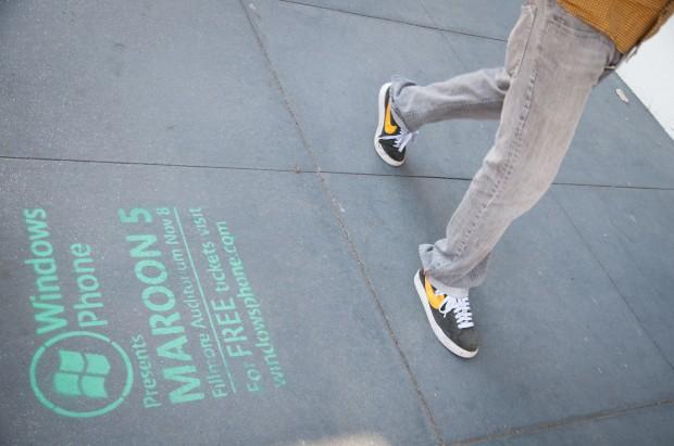 A pedestrian walks by Microsoft stenciled graffiti on the sidewalk in front of 740 Valencia Street. Photo by Jessica Lum