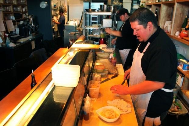 Tim Archuleta of Ichi Sushi, right, preps fish inside his new restaurant.
