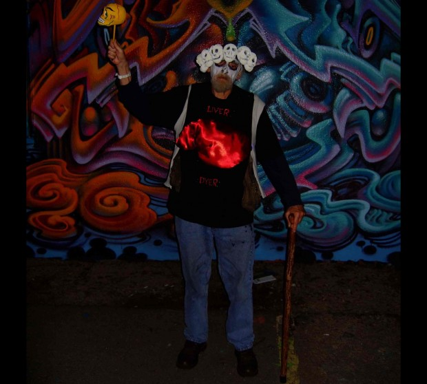 """Ross on the Day of the Dead in 2010, at 24th and Capp streets.  His shirt reads """"liver dyer,"""" with a fake liver sewn on.  (Ever humorous, he had a real beef liver taped to his back.)  Photo by Elizabeth Bell."""