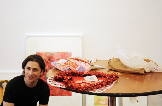 Alex Farkas next to a tinsel heart slated to decorate the launch party for Paperwork.