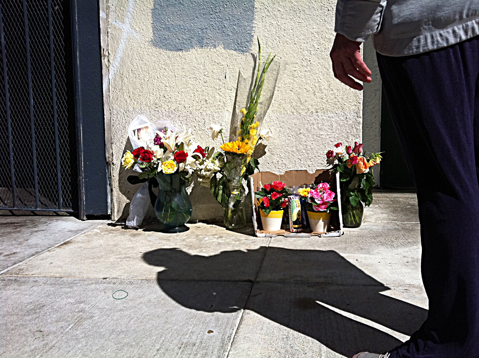 Friends of slain Gaspar Puch-Tzek have left flowers and candles next to where the Hog & Rocks cook was shot on Aug. 30. Photo by Helene Goupil