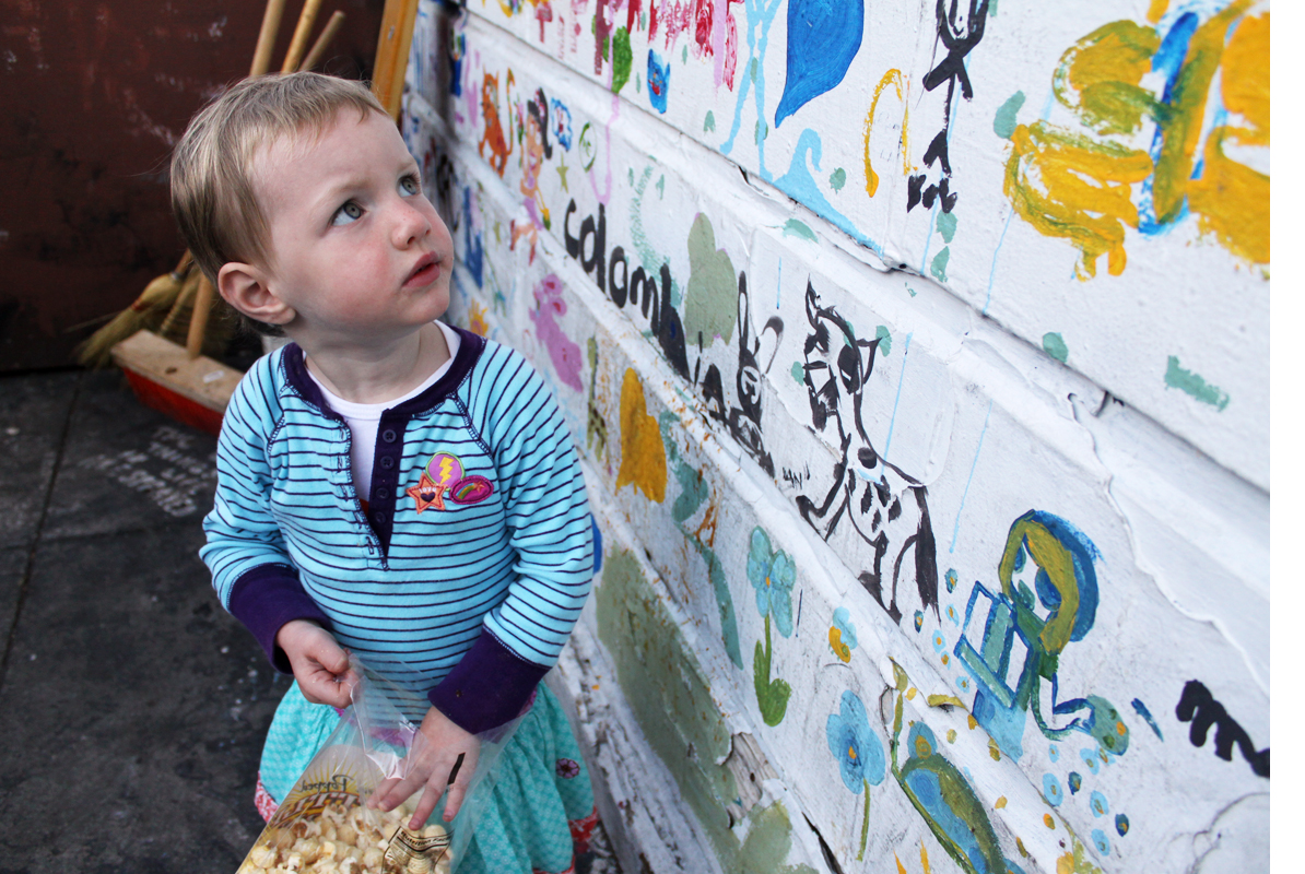 """Edda glances at the colorful images within the """"Mission Community Mural Project."""""""