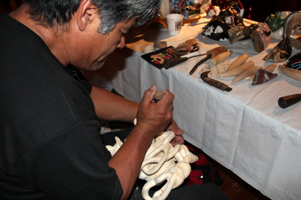Mexican Mask maker, Felipe Horta, intently focuses on chiseling away his elaborate devil mask.