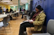 Gregory reads a newspaper as he sits with others at the Mission Neighborhood Resource Center Wednesday.